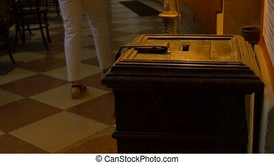 Donations Box in Church - A wooden old donation box in a...