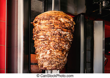 Doner Kebab On Rotating Vertical Spit - A close-up shot of...