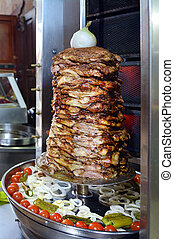 Doner kebab roasted on rotating spit. Food background texture.