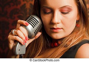 donna, abbracciato, mano, vendemmia, microfono, disposto, su, uno, stand., testa girata, a, uno, side., occhi chiusero