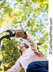 donna, andando bicicletta bicicletta, osservato, da, sotto, fuoco, a, lei, mano