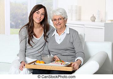 donna, carer, seduta, divano, anziano, pranzo, casa, vassoio