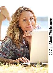 donna, computer portatile, usando, erba, dire bugie