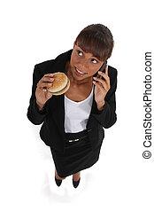 donna d'affari, mangiare, uno, hamburger, e, parlare, su, lei, cellula