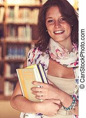 donna eretta, sorridente, studente, biblioteca