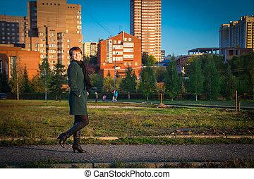 donna felice, in, uno, scuro, cappotto, camminare, fuori, autunno, a, tramonto