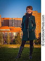 donna felice, in, uno, scuro, cappotto, standing, fuori, autunno, a, tramonto