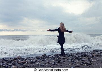 donna, in, uno, cappotto nero, spiaggia