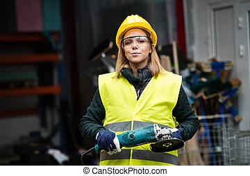 donna, lavoratore, con, angolo, macinatore, in, uno, warehouse.