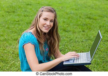 donna, lei, campagna, laptop, giovane guardare, mentre, macchina fotografica, usando, diritto