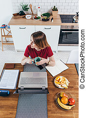 donna, lei, tazza, laptop, seduta, kitchen., presa a terra, fronte, tavola