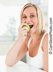 donna mangia, mela, seduta, giovane guardare, mentre, macchina fotografica, tavola verde, cucina