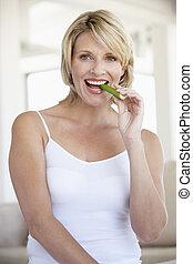 donna mangia, mezzo, sedano, macchina fotografica, bastone, sorridente, adulto