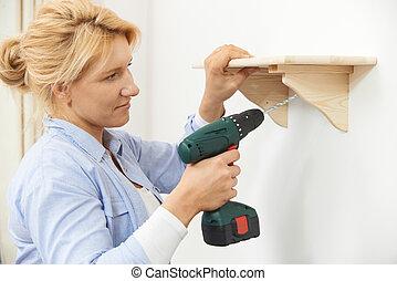 donna, mettere, legno, mensola, a casa, usando, trapano filo