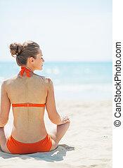 donna sedendo, giovane, spiaggia., vista posteriore