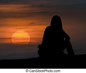 donna sedendo, guardando tramonto