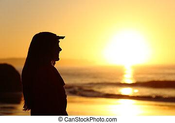 donna, silhouette, guardando avanti, a, tramonto