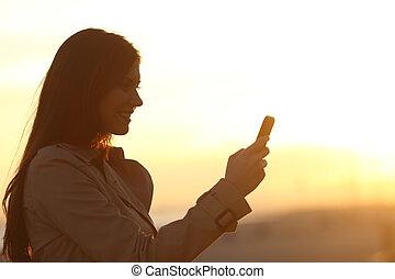 donna, silhouette, usando, uno, far male, telefono, a, tramonto