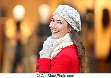donna sorridente, macchina fotografica, in, inverno, in, uno, centro commerciale