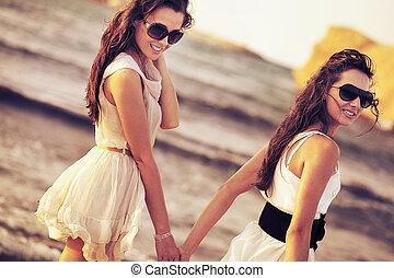 donna sorridente, spiaggia, due