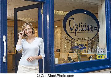 donna stando piedi, a, entrata anteriore, di, optometrists,...