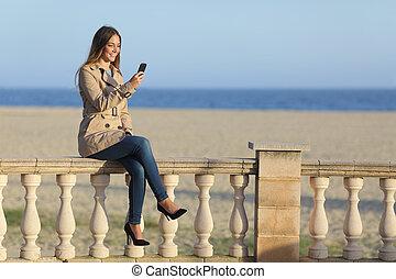 donna, texting, in, uno, far male, telefono, spiaggia