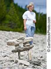 donna, tipo, inukshuk, dietro, statua, anziano, spiaggia