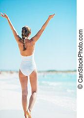 donna, tripudio, giovane, spiaggia., vista posteriore