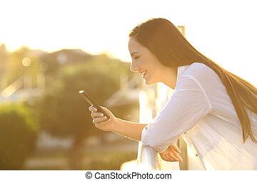 donna, usando, uno, far male, telefono, a, tramonto, in, uno, balcone