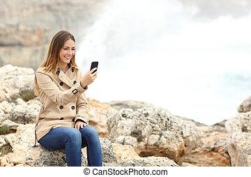 donna, usando, uno, far male, telefono, spiaggia, in, inverno