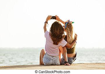 donne, seduta, fuori, spiaggia, prendere, uno, selfie.