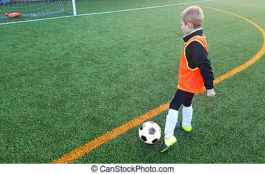 donner coup pied, garçon, habillement, formation, joueur, équipement, jouant football, sports, football., balle, pitch., jeune enfant