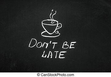 Don't be late message handwritten on the blackboard