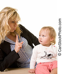 Adorable baby girl toddler with something in her mouth and mother shaking finger at her to tell her not to eat it