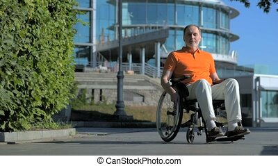 Pleasant senior man sitting in the wheelchair outdoors