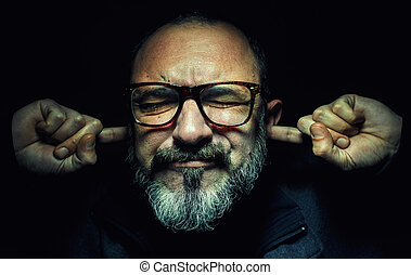 Portrait of an older man, wearing glasses, with fingers in ears, eyes closed tight.