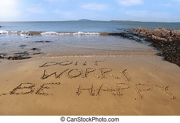 dont worry be happy inscribed on the beach with waves in the...