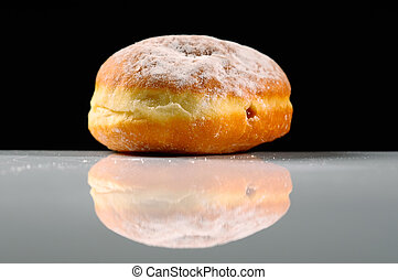 A fresh doughnut filled with jam and coated with sugar