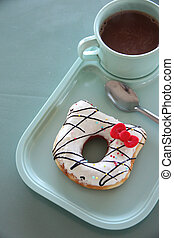 Donut and hot cocoa in a blue dish.
