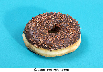 Donut covered with sweet chocolate icing on a blue background