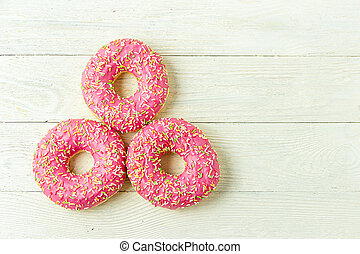 Donut on a wooden table. Photo of sweets with copyspace. Top view.