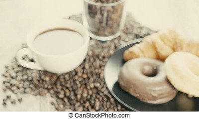 Donuts and cup of coffee on roasted coffee beans - Delicious...