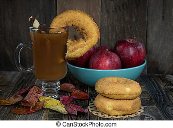 donuts and hot apple cider on rustic wood