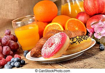 Donuts, croissant, orange juice, blueberries, raspberries, apples - sweet breakfast on wooden table