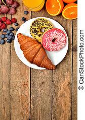 Donuts, croissant, orange juice, blueberries, raspberries, apples - sweet breakfast on wooden table - view from above