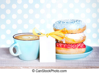 Donuts & cup coffee on wooden table background.