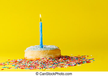 Fun birthday donut with candle on brigth yellow background