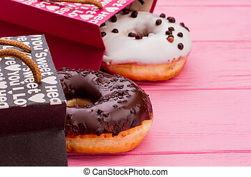 Donuts on pink wooden background.