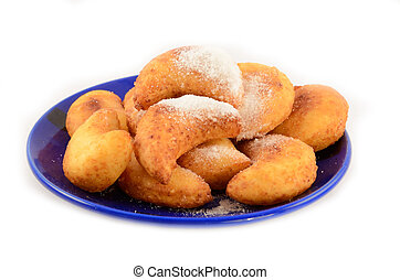 Sweet cottage cheese donuts in powder on a dark blue plate