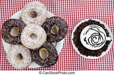 Donuts with coffee on table.